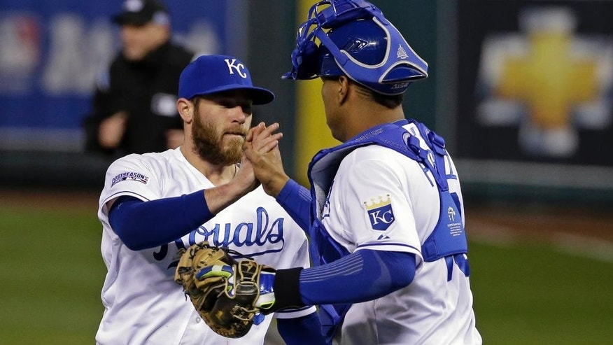 Kansas City Royals relief pitcher Greg Holland is congratulated by Salvador Perez following Game 3 of the American League baseball championship series Tuesday, Oct. 14, 2014, in Kansas City, Mo. The Royals won 2-1 and lead the series 3-0. (AP Photo/Matt Slocum )