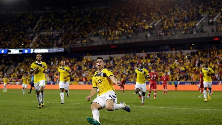 Colombia's James Rodriguez, center, begins to slide while celebrating his goal against Canada during the second half of an international soccer friendly match, Tuesday, Oct. 14, 2014, in Harrison, N.J. (AP Photo/Julio Cortez)
