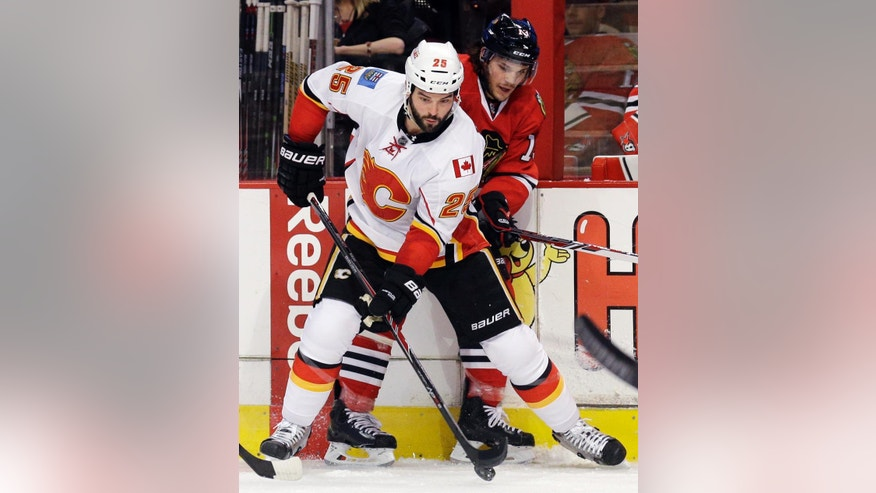 Calgary Flames left wing Brandon Bollig (25) controls the puck against Chicago Blackhawks left wing Daniel Carcillo during the first period of an NHL hockey game in Chicago, Wednesday, Oct. 15, 2014. (AP Photo/Nam Y. Huh)