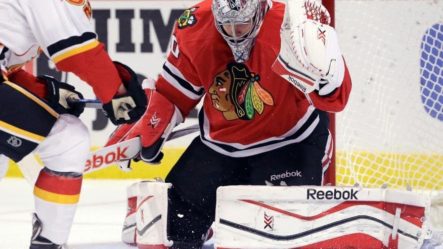 Chicago Blackhawks goalie Corey Crawfod, right, blocks a shot by Calgary Flames center Paul Byron (32) during the first period of an NHL hockey game in Chicago, Wednesday, Oct. 15, 2014. (AP Photo/Nam Y. Huh)