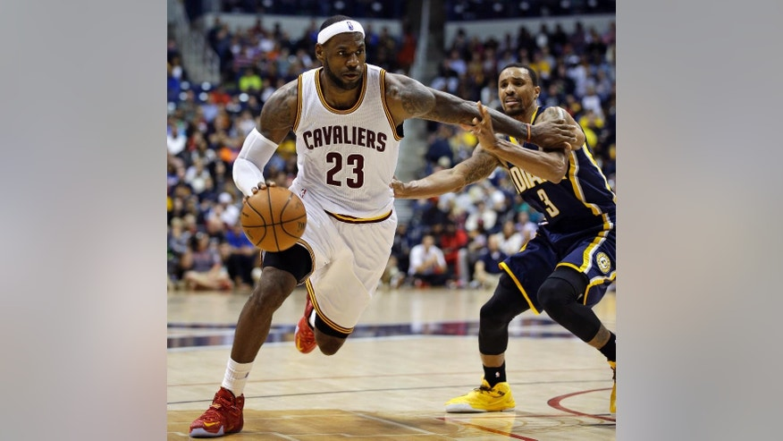 Cleveland Cavaliers forward LeBron James (23) drives past Indiana Pacers guard George Hill (3) in the second half of an NBA preseason basketball game, Wednesday, Oct. 15, 2014, in Cincinnati. Cleveland won 98-93. (AP Photo/Al Behrman)