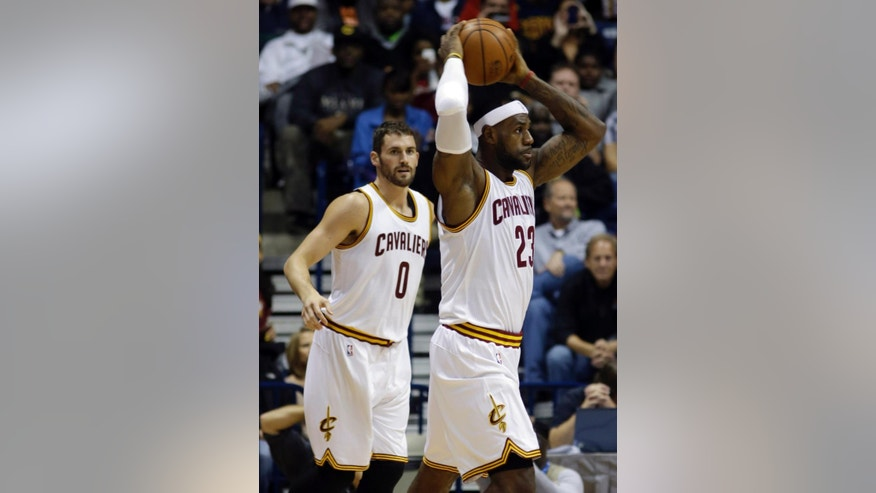 Cleveland Cavaliers forward LeBron James (23) looks to pass against the Indiana Pacers in the first half of an NBA preseason basketball game, Wednesday, Oct. 15, 2014, in Cincinnati. Cavaliers forward Kevin Love (0) watches. (AP Photo/Al Behrman)
