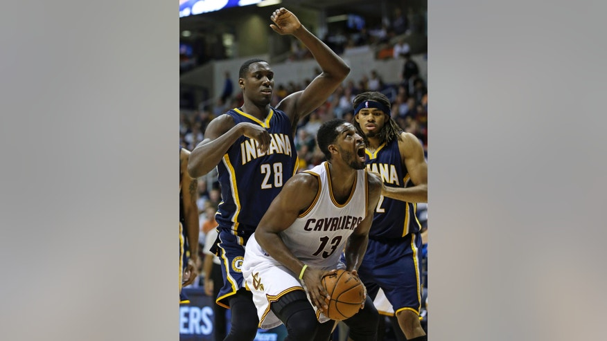 Cleveland Cavaliers forward Tristan Thompson (13) shoots against Indiana Pacers center Ian Mahinmi (28) and forward Chris Copeland in the second half of an NBA preseason basketball game, Wednesday, Oct. 15, 2014, in Cincinnati. Cleveland won 98-93. (AP Photo/Al Behrman)