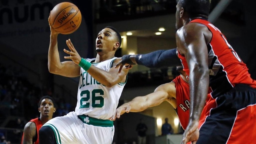 Boston Celtics guard Phil Pressey (26) drives through Toronto Raptors defenders during the first quarter of a preseason NBA basketball game in Portland, Maine, Wednesday, Oct. 15, 2014. (AP Photo/Elise Amendola)