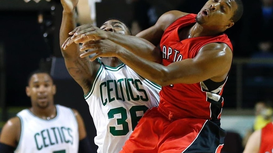 Boston Celtics guard Marcus Smart (36) and Toronto Raptors guard Kyle Lowry, right, grapple for a loose ball during the first quarter of a preseason NBA basketball game in Portland, Maine, Wednesday, Oct. 15, 2014. (AP Photo/Elise Amendola)
