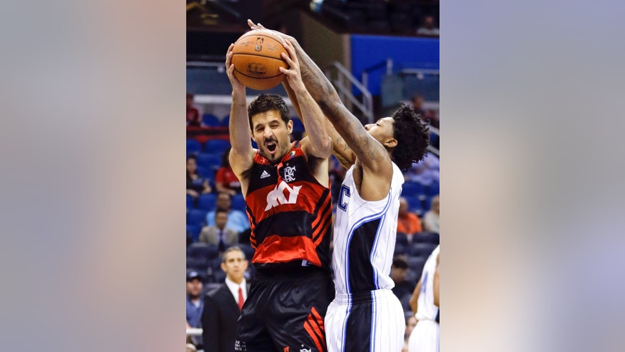 Orlando Magic's Elfrid Payton, right, blocks a shot-attempt by Flamengo Brazil's Nicolas Laprovittola, left, during the first half of an NBA preseason exhibition basketball game in Orlando, Fla., Wednesday, Oct. 15, 2014. (AP Photo/John Raoux)