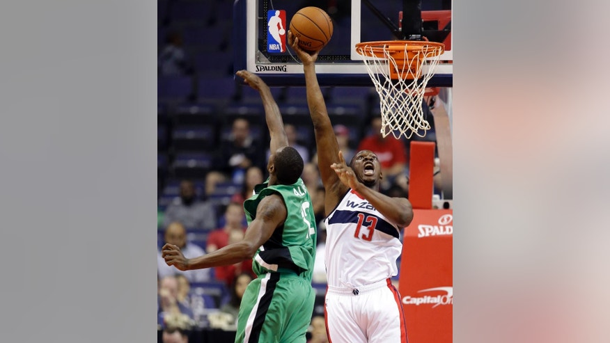 Washington Wizards center Kevin Seraphin (13), from France, shoots as Maccabi Haifa forward Jeff Allen (12) defends during the first half of an exhibition NBA basketball game, Wednesday, Oct. 15, 2014, in Washington. (AP Photo/Alex Brandon)