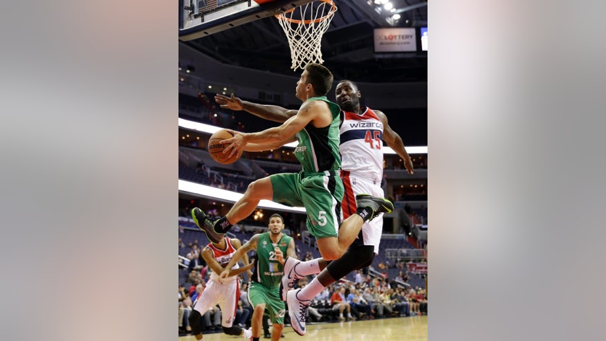 Maccabi Haifa guard Brody Angley (5) goes under the basket to shoot as Washington Wizards center DeJuan Blair (45) defends during the first half of a preseason NBA basketball game, Wednesday, Oct. 15, 2014, in Washington. (AP Photo/Alex Brandon)