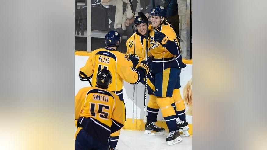 Nashville Predators center Filip Forsberg (9) celebrates with center Derek Roy (21), defenseman Ryan Ellis (4) and center Craig Smith (15) after Forsberg scored against the Calgary Flames in the first period of an NHL hockey game Tuesday, Oct. 14, 2014, in Nashville, Tenn.  (AP Photo/Mark Zaleski)