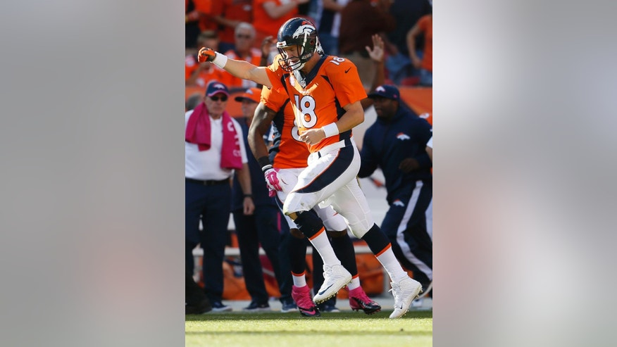 FILE - In this Oct. 5, 2014, file photo, Denver Broncos quarterback Peyton Manning (18) runs upfield after a touchdown pass against the Arizona Cardinals during the second half of an NFL football game in Denver. Next Sunday, Oct. 19, 2014,  against San Francisco, or perhaps the following Thursday against San Diego, Manning will surpass Brett Favre's NFL record 508 touchdown passes. Manning is two shy after throwing for three scores in a 31-17 victory over the New York Jets on Sunday. (AP Photo/Joe Mahoney, File)