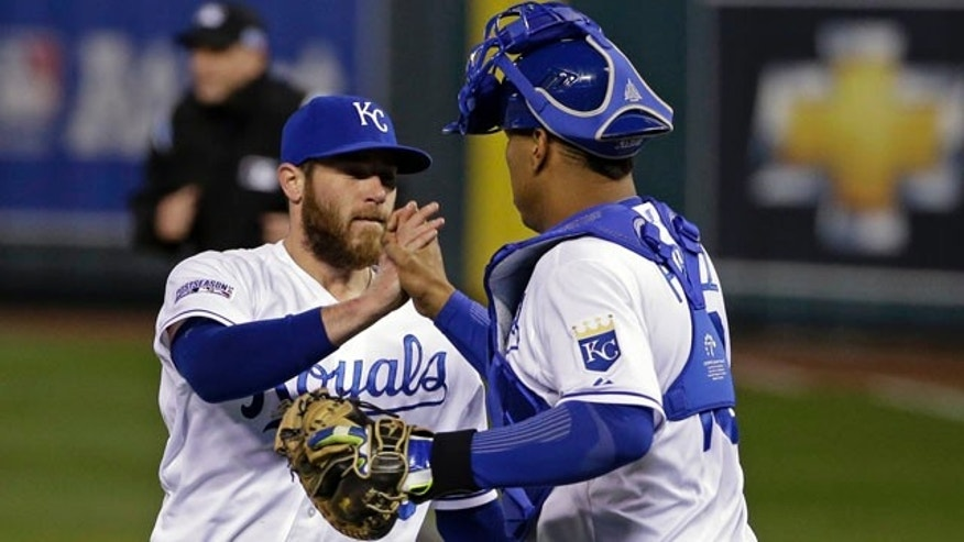 October 14, 2014: Kansas City Royals relief pitcher Greg Holland is congratulated by Salvador Perez following Game 3 of the American League baseball championship series, in Kansas City, Mo. (AP Photo/Matt Slocum )