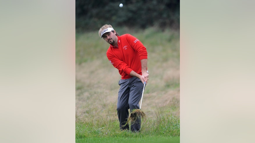 France's Victor Dubuisson  plays from the rough during day one of the World Match Play Championship at The London Club, in Ash southeast England Wednesday Oct. 15, 2014. (AP Photo/Nigel French/PA) UNITED KINGDOM OUT