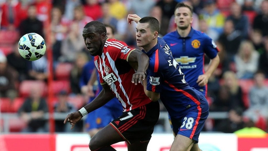 FILE - In this Aug. 24, 2014, file photo, Sunderland's Jozy Altidore, left, vies for the ball with Manchester United's Micheal Keane, right, during their English Premier League soccer match at the Stadium of Light in Sunderland, England. Following the fortunes of American players on top clubs in Europe's best leagues doesn't take much time these days. Altidore, the top U.S. forward, hasn't started a single one of Sunderland's seven Premier League games and has appeared in four as a second-half sub. (AP Photo/Scott Heppell, File)