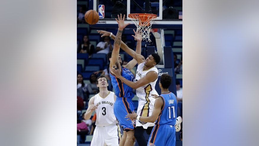 New Orleans Pelicans forward Anthony Davis, right, swats the ball away from Oklahoma City Thunder center Steven Adams in the first half of an NBA preseason basketball game in New Orleans, Thursday, Oct. 16, 2014. (AP Photo/Gerald Herbert)