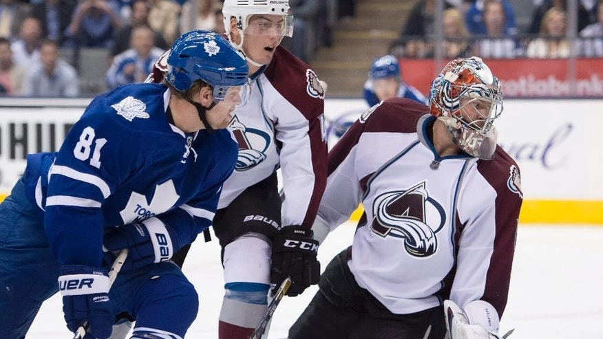 Toronto Maple Leafs' Phil Kessel (81) and Colorado Avalanche goaltender Semyon Varlamov and defenseman Tyson Barrie (4) look at the puck in the net on Kessel's game-winning goal in overtime of an NHL hockey game Tuesday, Oct. 14, 2014, in Toronto. (AP Photo/The Canadian Press, Frank Gunn)