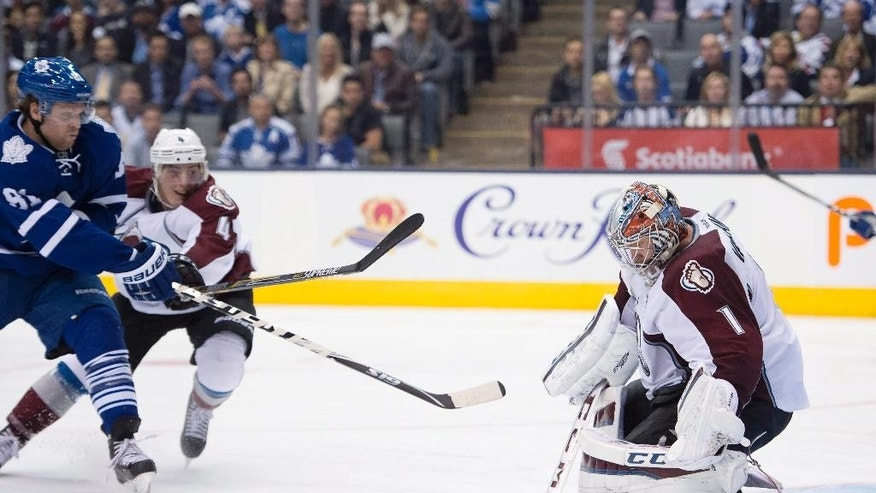 Toronto Maple Leafs' Phil Kessel (81) scores the game winning-goal on Colorado Avalanche goaltender Semyon Varlamov as Tyson Barrie defends during overtime of an NHL hockey game Tuesday, Oct. 14, 2014, in Toronto. (AP Photo/The Canadian Press, Frank Gunn)