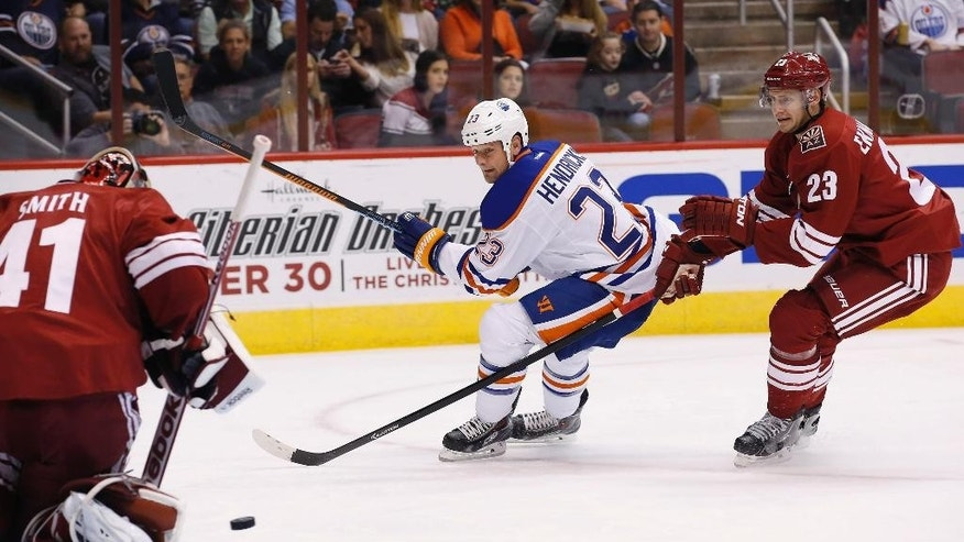 Arizona Coyotes' Mike Smith (41) makes a save on a shot by Edmonton Oilers' Matt Hendricks, middle, as Coyotes' Oliver Ekman-Larsson, right, defends during the first period of an NHL hockey game Wednesday, Oct. 15, 2014, in Glendale, Ariz. (AP Photo/Ross D. Franklin)