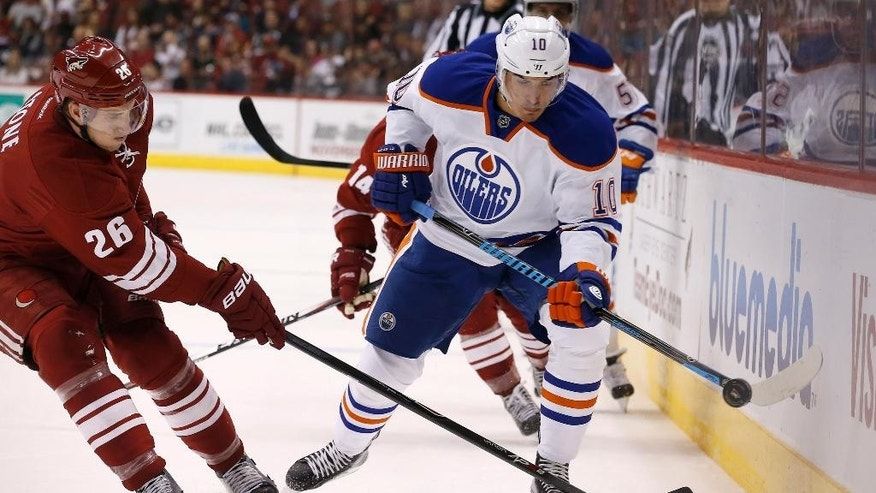 Edmonton Oilers' Nail Yakupov (10), of Russia, flips the puck away from Arizona Coyotes' Michael Stone (26) during the first period of an NHL hockey game Wednesday, Oct. 15, 2014, in Glendale, Ariz. (AP Photo/Ross D. Franklin)