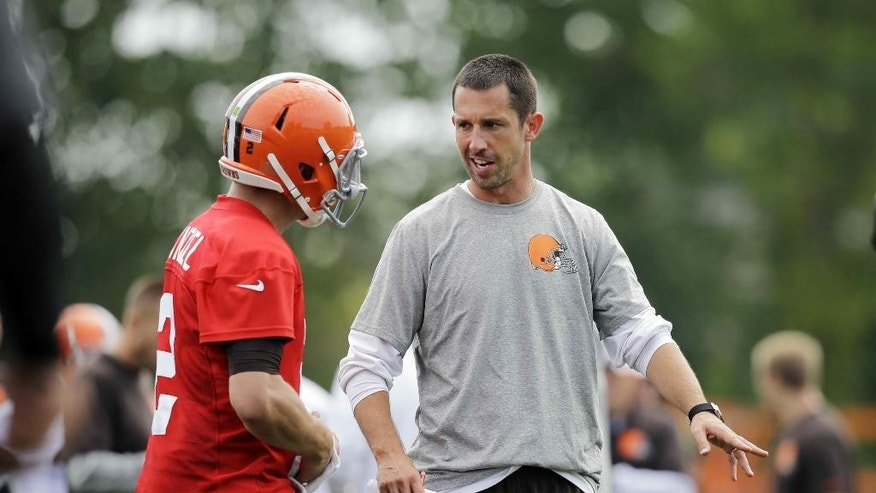 FILE - In this July 26, 2014, file photo, Cleveland Browns offensive coordinator Kyle Shanahan talks to quarterback Johnny Manziel at the NFL football team's training camp in Berea, Ohio. Shanahan's imaginative offense has the Browns off to a great start and the son of former NFL coach Mike Shanahan has had a rebirth in Cleveland. (AP Photo/Mark Duncan, File)