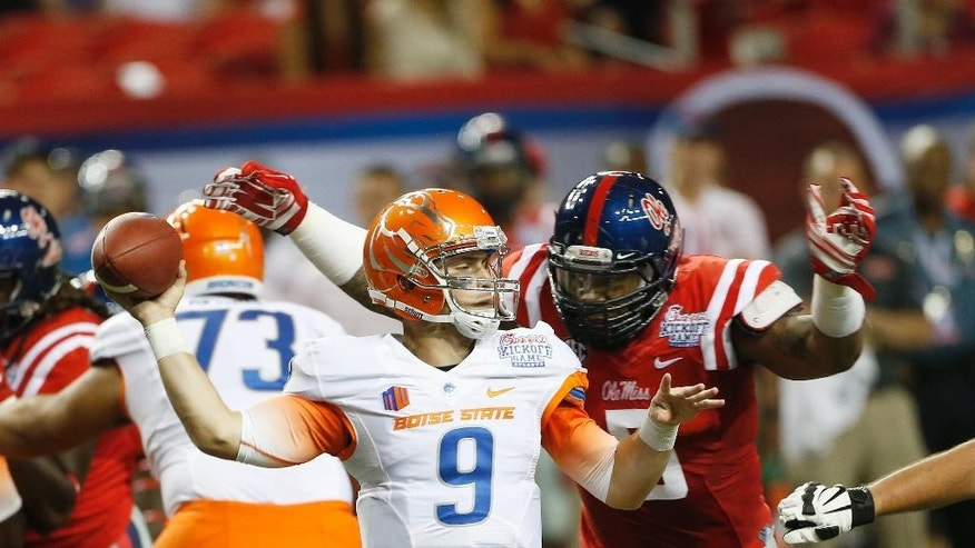 FILE - In this Aug. 28, 2014, file photo, Boise State quarterback Grant Hedrick (9) throws under pressure from Mississippi defensive tackle Robert Nkemdiche (5)) in the first half of an NCAA college football game in Atlanta. The Rebels have rocketed from an SEC afterthought to the No. 3 team in the country by bringing in better talent, starting with a talented sophomore class that includes Robert Nkemdiche, Laquon Treadwell and Laremy Tunsil. (AP Photo/John Bazemore, File)