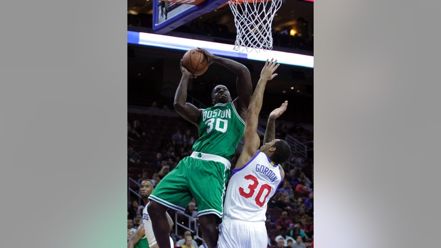 Boston Celtics' Brandon Bass, left, shoots over Philadelphia 76ers' Drew Gordon in the first half of a preseason NBA basketball game Thursday, Oct. 16, 2014, in Philadelphia. (AP Photo/H. Rumph Jr)
