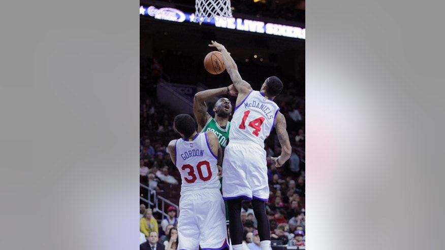 Boston Celtics' Marcus Thornton, center, has his shot stopped by Philadelphia 76ers' Drew Gordon (30) and K.J. McDaniels (14) in the first half of a preseason NBA basketball game Thursday, Oct. 16, 2014, in Philadelphia. (AP Photo/H. Rumph Jr)