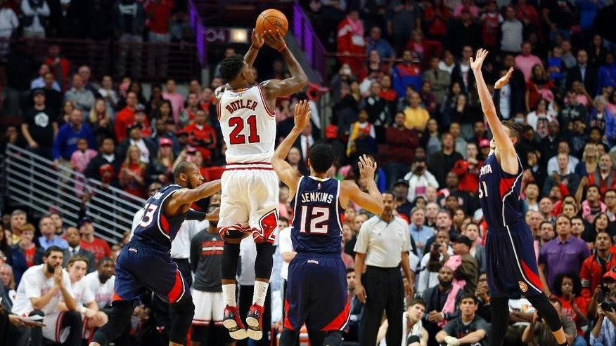 Chicago Bulls guard Jimmy Butler (21) shoot the game-winning 3-point basket against the Atlanta Hawks during the second half of a preseason NBA basketball game in Chicago on Thursday Oct. 16, 2014. The Bulls won 85-84. (AP Photo/Jeff Haynes)
