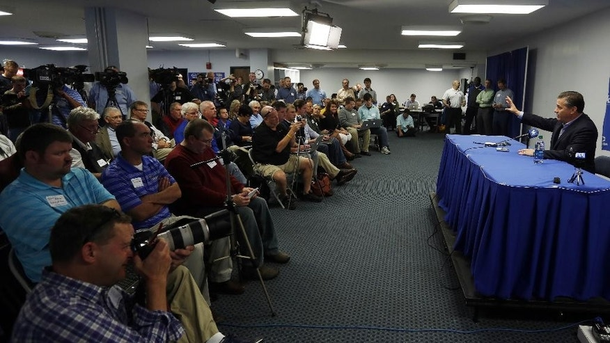 Kentucky head coach John Calipari, right, speaks to reporters during the team's NCAA college basketball media day, Thursday, Oct. 16, 2014, in Lexington, Ky. (AP Photo/James Crisp)