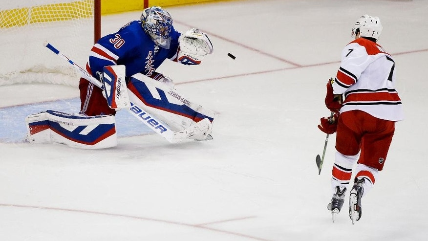 New York Rangers goalie Henrik Lundqvist (30), of Sweden, stops a shot by Carolina Hurricanes' Ryan Murphy (7) during the shootout in an NHL hockey game Thursday, Oct. 16, 2014, in New York. The Rangers won 2-1. (AP Photo/Frank Franklin II)