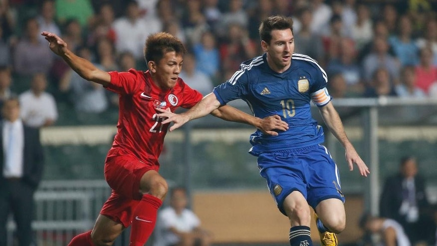 Argentina's Lionel Messi, right, fights for the ball with Hong Kong's Kwok Kin Pong during a friendly soccer match in Hong Kong Tuesday, Oct. 14, 2014. (AP Photo/Kin Cheung)