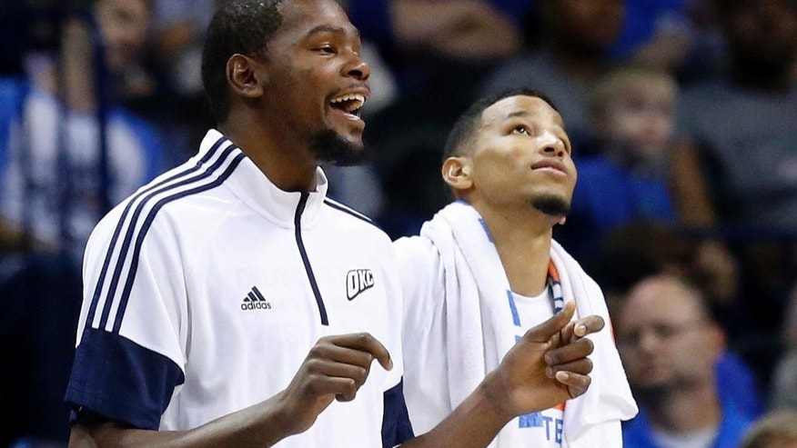 Injured Oklahoma City Thunder forward Kevin Durant, left, cheers on the sidelines in the fourth quarter of an NBA basketball pre-season game in Oklahoma City, Tuesday, Oct. 14, 2014. Oklahoma City won 117-107. Forward Andre Roberson is at right. (AP Photo/Sue Ogrocki)