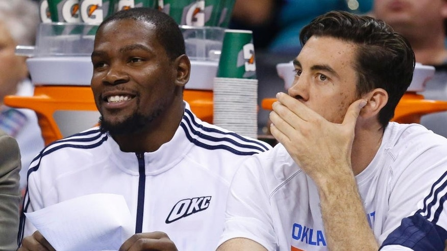 Oklahoma City Thunder forward Kevin Durant, left, and forward Nick Collison, right, watch from the bench in the second quarter of an NBA basketball pre-season game against the Memphis Grizzlies in Oklahoma City, Tuesday, Oct. 14, 2014. Durant is out with a fractured foot. (AP Photo/Sue Ogrocki)