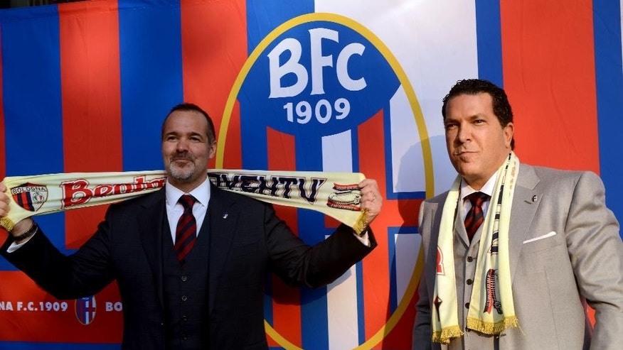 Joe Tacopina, right, and Joey Saputo pose in front of the Bologna Football Club logo, in Bologna, Italy, Thursday, Oct. 16, 2014. A group of North Americans led by New York lawyer Joe Tacopina were presented Thursday as the new owners of Italy's cash-strapped Serie B soccer club Bologna. Tacopina was named club president and Montreal Impact president Joey Saputo is a large investor. Tacopina, who represents New York Yankees slugger Alex Rodriguez in his drug case, resigned from his position on Roma's board to pursue the Bologna deal. (AP Photo/Gianfilippo Oggioni)