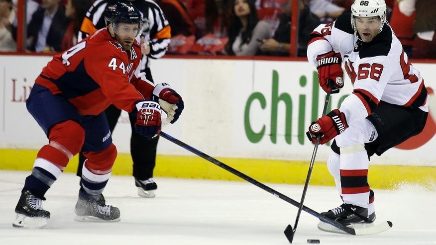 New Jersey Devils right wing Jaromir Jagr (68), from the Czech Republic, controls the puck as Washington Capitals defenseman Brooks Orpik (44) defends in the first period of an NHL hockey game, Thursday, Oct. 16, 2014, in Washington. (AP Photo/Alex Brandon)