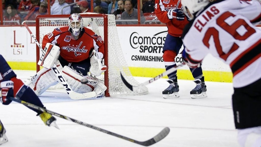 Washington Capitals goalie Braden Holtby (70) prepares to block a shot by New Jersey Devils left wing Patrik Elias (26), from the Czech Republic, in the second period of an NHL hockey game, Thursday, Oct. 16, 2014, in Washington. (AP Photo/Alex Brandon)