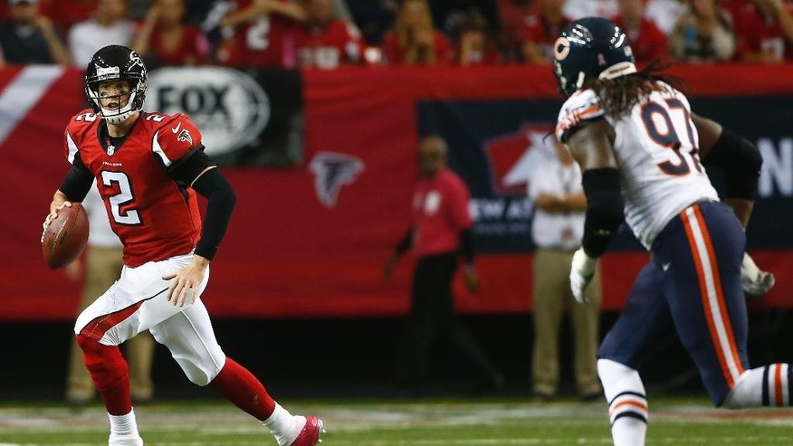 Atlanta Falcons quarterback Matt Ryan (2) moves out of the pocket as Chicago Bears defensive end Willie Young (97) looks on during the second half of an NFL football game, Sunday, Oct. 12, 2014, in Atlanta. (AP Photo/John Bazemore)