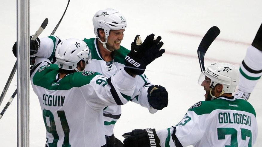 Dallas Stars' Tyler Seguin (91) celebrates his game-winning goal with Jamie Benn (14) and Alex Goligoski (33) in the final seconds of an NHL hockey game against the Pittsburgh Penguins in Pittsburgh, Thursday, Oct. 16, 2014. The Stars won 3-2. (AP Photo/Gene J. Puskar)