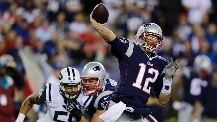 New England Patriots quarterback Tom Brady throws as New York Jets defensive end Jason Babin (58) pursues during the first half of an NFL football game Thursday, Oct. 16, 2014, in Foxborough, Mass. (AP Photo/Charles Krupa)