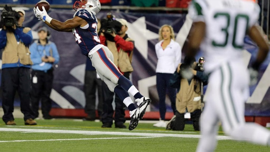 New England Patriots running back Shane Vereen catches a pass for a touchdown from quarterback Tom Brady as New York Jets cornerback Darrin Walls (30) watches during the first half of an NFL football game Thursday, Oct. 16, 2014, in Foxborough, Mass. (AP Photo/Charles Krupa)