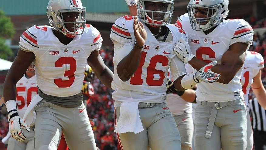FILE - In this Oct. 4, 2011, file photo, Ohio State's J.T. Barrett, center, celebrates his touchdown against Maryland with Evan Spencer, right, and Michael Thomas during the second half of an NCAA college football game in College Park, Md. Many were surprised when redshirt freshman Barrett was ordained in the preseason as the backup quarterback for Ohio State. Absolutely no one expected what happened when he stepped in when Braxton Miller was lost for the season with a shoulder injury.(AP Photo/Gail Burton, File)