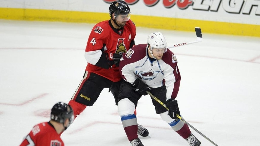 Colorado Avalanche's John Mitchell, right, works against Ottawa Senators' Chris Phillips (4) during the second period of an NHL hockey game Thursday, Oct. 16, 2014, in Ottawa, Ontario. (AP Photo/The Canadian Press, Justin Tang)