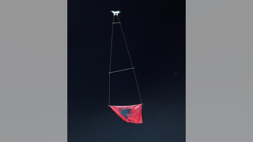 A drone flies an Albanian flag at the national league match in Vlora, 140 kilometers (85 miles) southwest of capital Tirana, between local Flamurtari FC vs. KF Skenderbeu, Friday, Oct. 17, 2014. The game ended 1-1. Earlier this week a drone that flew an Albanian nationalist banner over a soccer stadium in Belgrade, Serbia ignited a brawl when Albanian players who tried to protect it were attacked by Serb counterparts, fans and security staff on the pitch, forcing the referee to abandon the match. (AP Photo/str)