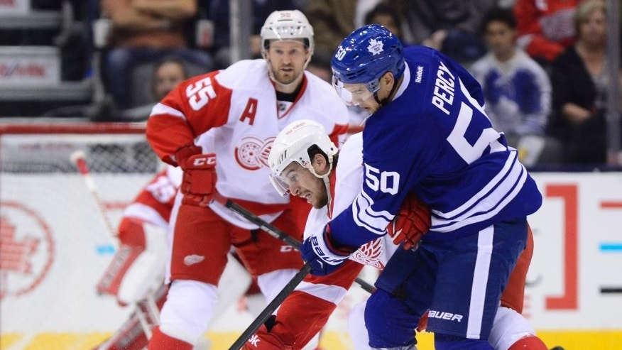 Toronto Maple Leafs' Stuart Percy (50) and Detroit Red Wings' Brendan Smith battle for the puck during first-period NHL hockey game action in Toronto, Friday, Oct. 17, 2014. (AP Photo/The Canadian Press, Frank Gunn)