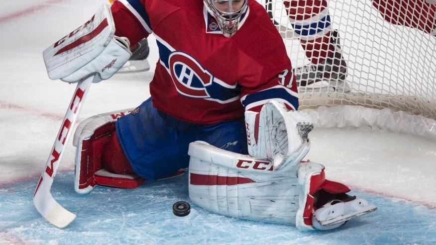 Montreal Canadiens goalie Carey Price stops the puck against the Boston Bruins during first-period NHL hockey game action Thursday, Oct. 16, 2014, in Montreal. (AP Photo/The Canadian Press, Paul Chiasson)