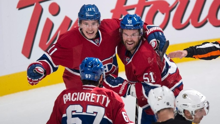Montreal Canadiens' Brendan Gallagher, left, and David Desharnais celebrate a power-play goal by teammate Max Pacioretty against the Boston Bruins during first-period NHL hockey game action Thursday, Oct. 16, 2014, in Montreal. (AP Photo/The Canadian Press, Paul Chiasson)