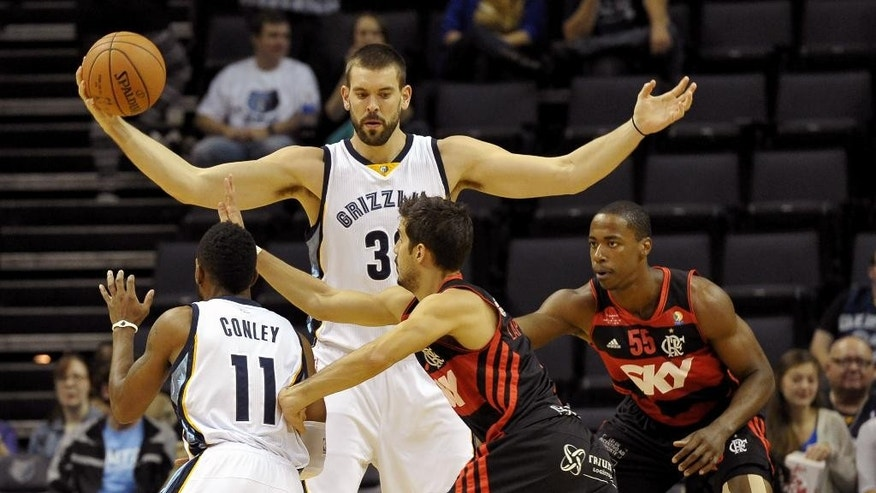 Memphis Grizzlies center Marc Gasol, top, controls the ball while Grizzlies guard Mike Conley (11), Flamengo guard Nicolas Laprovittola, front center, and Flamengo center Jerome Meyinsse (55) struggle for position in the first half of a preseason NBA basketball game Friday, Oct. 17, 2014, in Memphis, Tenn. (AP Photo/Brandon Dill)