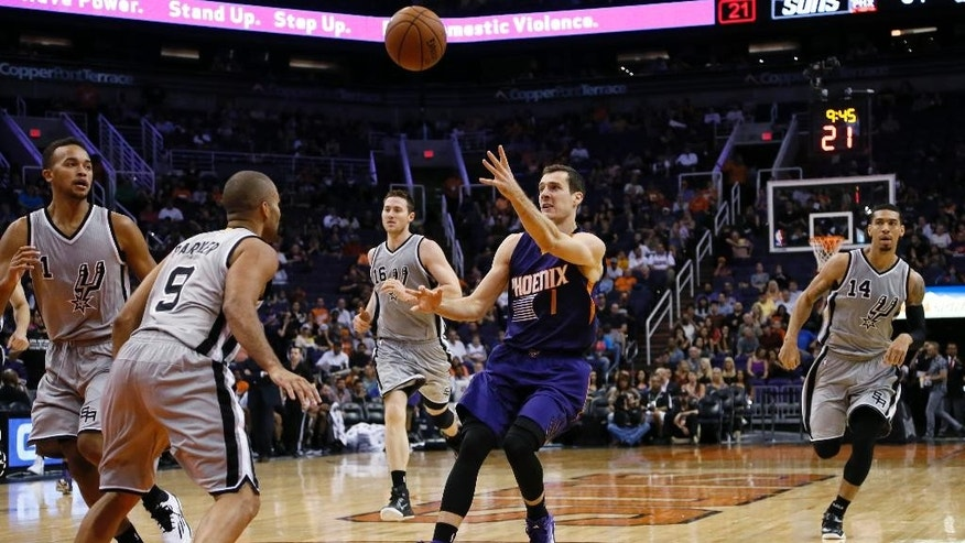 Phoenix Suns guard Goran Dragic (1), of Slovenia, passes the ball as San Antonio Spurs' Tony Parker (9), Kyle Anderson, left, Danny Green (14) and Aron Baynes (16) defend during the second half of an NBA preseason basketball game, Thursday, Oct. 16, 2014, in Phoenix. (AP Photo/Matt York)