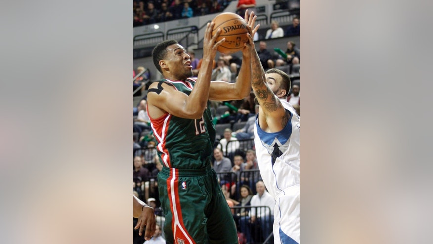 Milwaukee Bucks forward Jabari Parker, left, drives to the basket past Minnesota Timberwolves center Nikola Pekovic during the first half of a preseason NBA basketball game, Friday, Oct. 17, 2014, in Cedar Rapids, Iowa. (AP Photo/Matthew Holst)