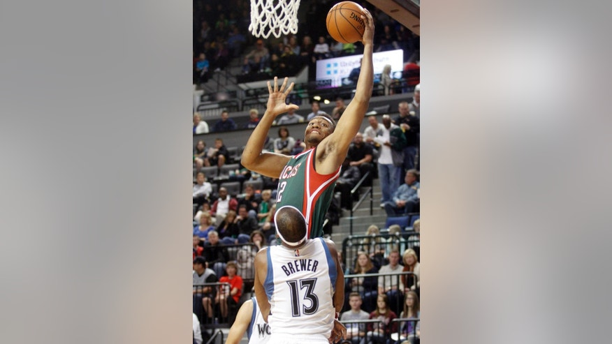 Milwaukee Bucks forward Jabari Parker, top, drives to the basket past Minnesota Timberwolves forward Corey Brewer during the first half of a preseason NBA basketball game, Friday, Oct. 17, 2014, in Cedar Rapids, Iowa. (AP Photo/Matthew Holst)