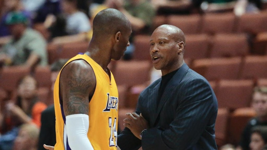 Los Angeles Lakers coach Byron Scott, right, talks to Kobe Bryant during the first half of a preseason NBA basketball game against the Utah Jazz on Thursday, Oct. 16, 2014, in Anaheim, Calif. (AP Photo/Jae C. Hong)